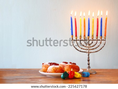 jewish holiday Hanukkah with menorah, doughnuts and wooden dreidels (spinning top).  - stock photo