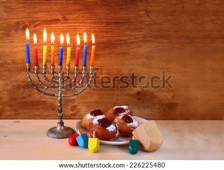 jewish holiday Hanukkah with menorah, doughnuts and wooden dreidels (spinning top).  - stock photo