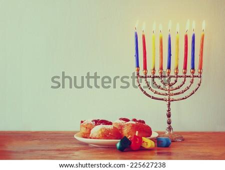 jewish holiday Hanukkah with menorah, doughnuts and wooden dreidels (spinning top). retro filtered image  - stock photo