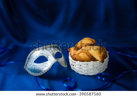 Jewish holiday of Purim. Hamantaschen cookies and carnival mask on dark blue silk background - stock photo