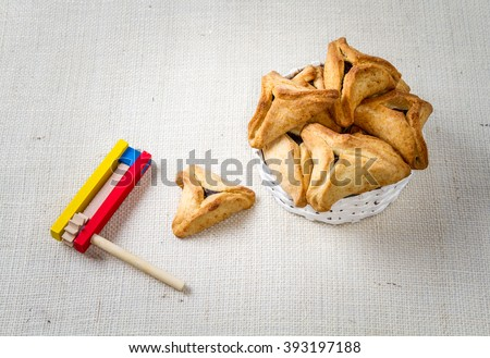 Jewish holiday of Purim. Hamantaschen cookies and wooden gragger - stock photo