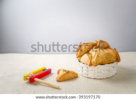 Jewish holiday of Purim. Hamantaschen cookies  and wooden gragger, free space for text - stock photo