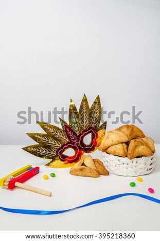 Jewish holiday of Purim. Hamantaschen cookies, gragger and carnival mask with free space for text - stock photo