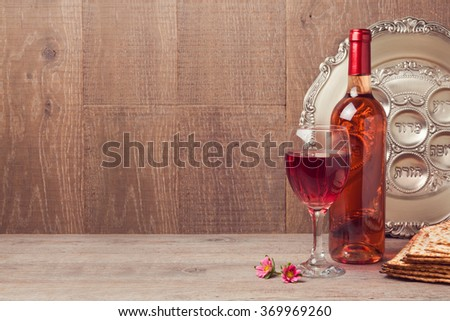 Jewish holiday Passover background with wine and seder plate on wooden table - stock photo