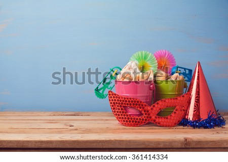 Jewish holiday purim background with carnival mask, hat and buckets - stock photo