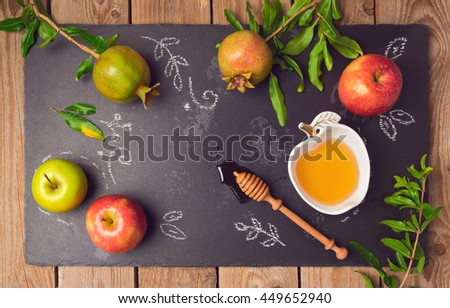 Jewish holiday Rosh Hashana background with apples, pomegranate and honey on blackboard. View from above. Flat lay