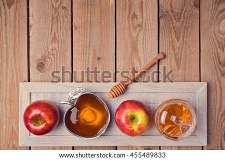 Jewish holiday Rosh Hashana background with honey and apples on wooden table. View from above. Flat lay