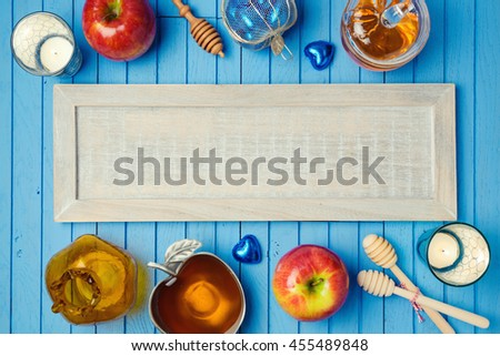 Jewish holiday Rosh Hashana background with wooden board, honey and apples on table. View from above. Flat lay