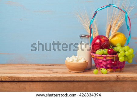Jewish holiday Shavuot background with milk bottle and fruit basket on wooden table - stock photo