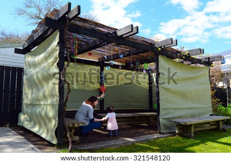 Jewish woman and child visiting their family Sukkah in the Jewish festival of Sukkot. A Sukkah is a temporary structure where meals are taken for the week. - stock photo