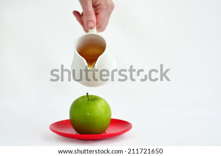 Jewish woman hand holds honey pot and pour fresh honey with on green apple during Rosh Hashanah Jewish holiday, on white background with copy space - stock photo