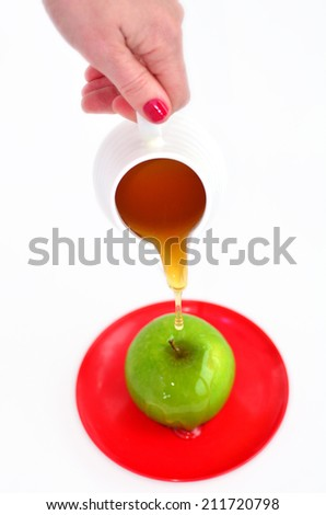 Jewish woman hand holds honey pot and ready to pour fresh honey with on green apple during Rosh Hashanah Jewish holiday, on white background with copy space - stock photo