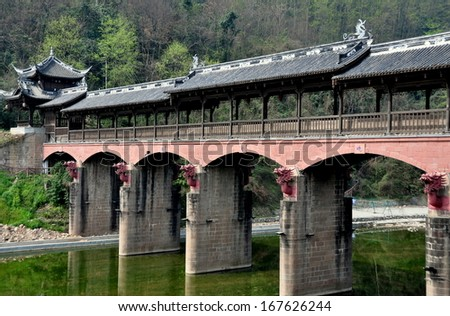 JIE ZI ANCIENT TOWN (SICHUAN), CHINA:   The handsome covered Dragon bridge, aptly named for its terra cotta dragon heads on each of its support towers - stock photo
