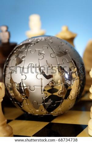 Jigsaw globe puzzle on chess board - stock photo