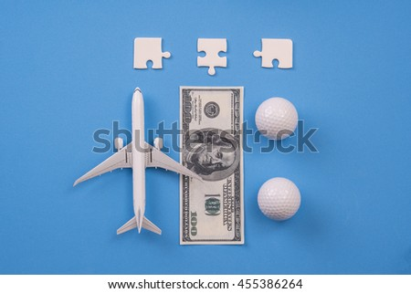 jigsaw, money and golf ball on blue background, Balance working concept. - stock photo