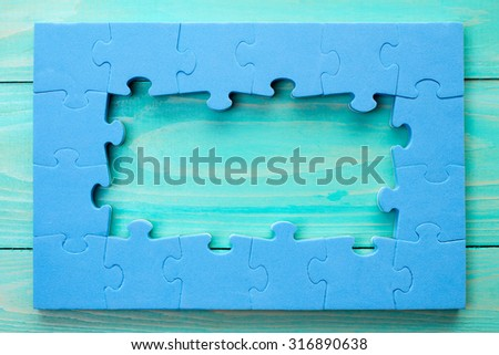 Jigsaw puzzle frame on blue wooden background - stock photo