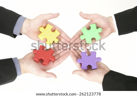 Jigsaw puzzle in business men's hands