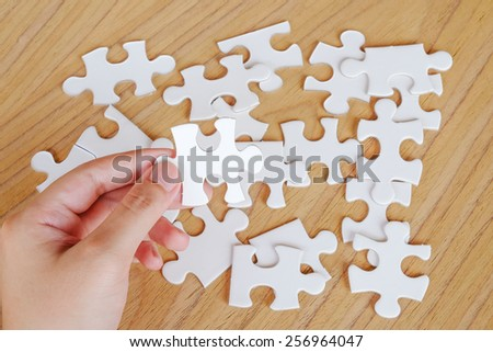 Jigsaw puzzle in hand, business background