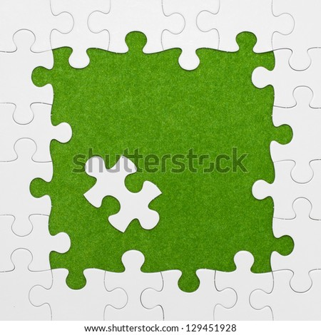 Jigsaw puzzle on green background - stock photo