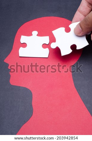 Jigsaw puzzle pieces and black paper project as a outline of human head - stock photo