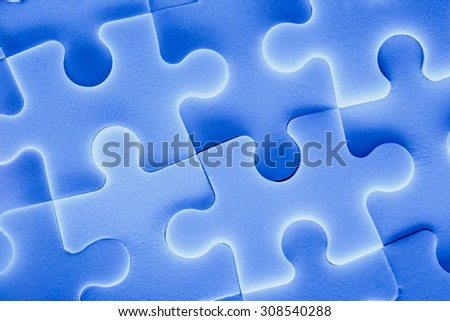 Jigsaw puzzle pieces as background in closeup - stock photo