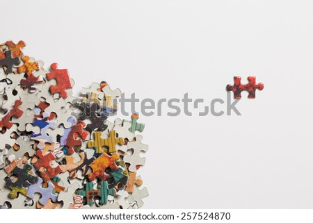 Jigsaw Puzzle Pieces In A Pile With Single Piece Separated On White Background