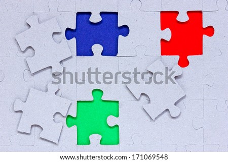 Jigsaw puzzle with different colored pieces signifying concepts of diversity, individuality and community  - stock photo