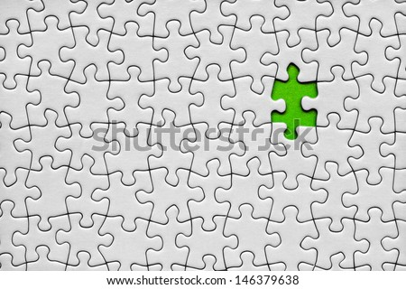 Jigsaw puzzle with one green piece missing - stock photo