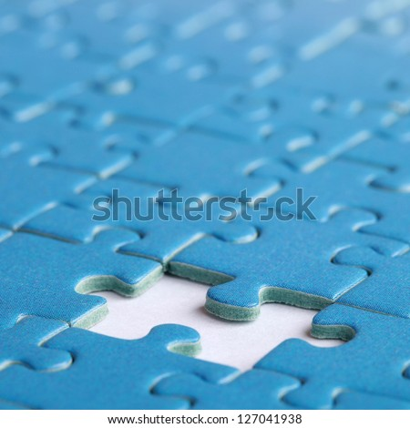 Jigsaw Puzzle with the missing piece, shallow depth of field - stock photo