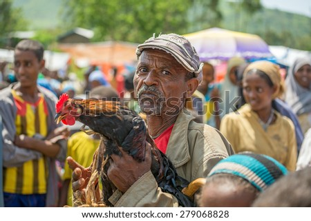 JIMMA, ETHIOPIA - MAY 2, 2015 : Old ethiopian man selling a rooster in a market.