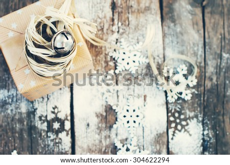 Jingle Hand Bell and Natural Twine as Decor on Christmas Box. Wooden Background with Snowflakes - stock photo