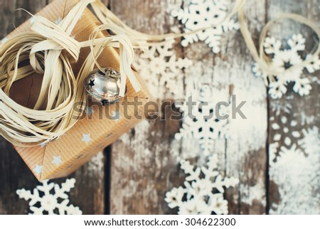 Jingle Hand Bell and Natural Twine as Decor on Christmas Box. Wooden Background with Snowflakes. Toned image - stock photo