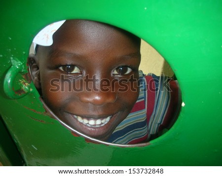 JINJA, UGANDA - JUNE 18: unidentified African boy, aged 7 years old, peeks at the camera through a gap in a metal door on June 18, 2010 in a tribal village on the outskirts of Jinja, Uganda. - stock photo