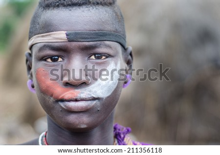 JINKA, ETHIOPIA - AUGUST 10: portrait of unidentified Mursi boy on August 10 2014. The men of Mursi tribe usually paint their bodies and faces with colored pigments - stock photo