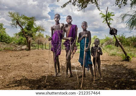 JINKA, ETHIOPIA - AUGUST 10: portrait of unidentified Mursi men on August 10 2014. Mursi people wear many ornament and paint their bodies - stock photo