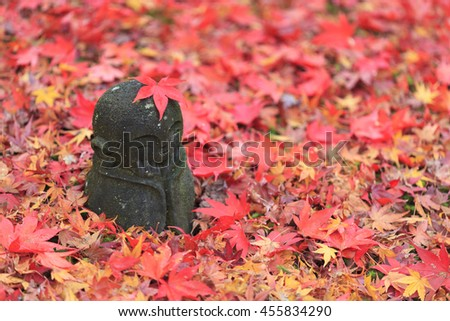 Jizo stone statue on the ground with colorful Japanese Maple leaves. (Selective focus)