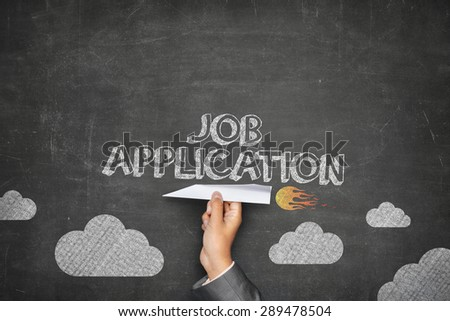 Job application concept on black blackboard with businessman hand holding paper plane - stock photo
