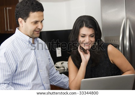 Job at home, lovely couple working in kitchen - stock photo