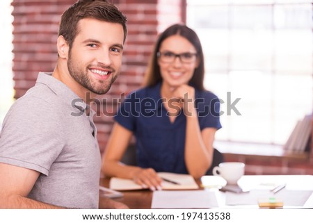 Job candidate. Handsome young man sitting at the table and looking over shoulder with smile while cheerful woman sitting in front of him  - stock photo