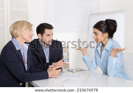 Job interview or business meeting: man and woman sitting at the table in the office talking together. - stock photo