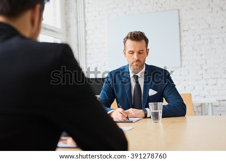 Job interview. Recruiter writing down candidate answers - stock photo