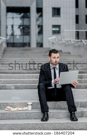 Job Search. Young man sitting on the street and keeps your computer in the hands.