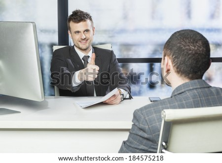 Job well done - concept , boss showing thumb up to one of his employee in the office - stock photo