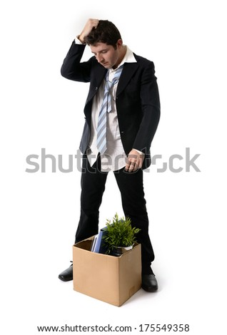 Jobless young Business Man with Cardboard Box Fired from Job isolated on White Background looking depressed, sad an in stress - stock photo