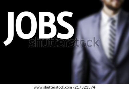 Jobs written on a board with a business man on background - stock photo