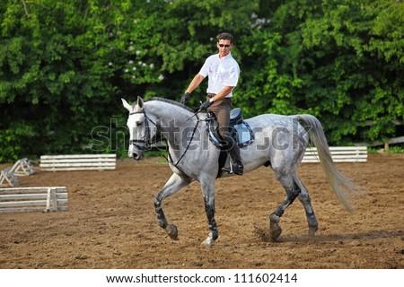 Jockey in glasses rides horse near barrier on hippodrome - stock photo