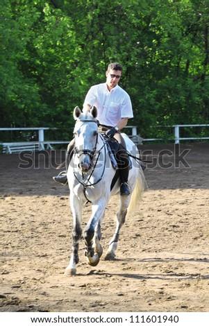 Jockey riding horse on hippodrome - stock photo
