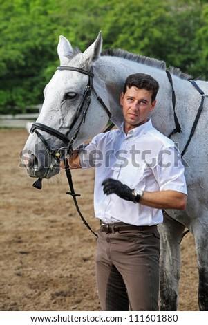 Jockey stand near horse on hippodrome - stock photo