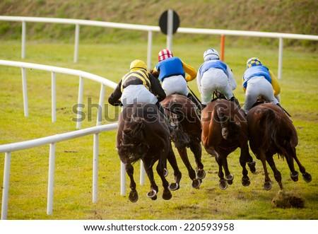 Jockeys on horses at the track. - stock photo