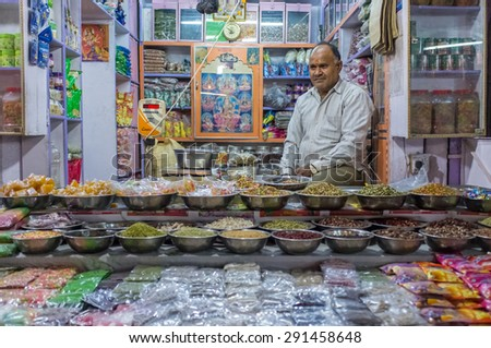 JODHPUR, INDIA - 10 FEBRUARY 2015: Candy shop owner sits while waiting for customers with large variety of mouth-fresheners and sweets on display. - stock photo